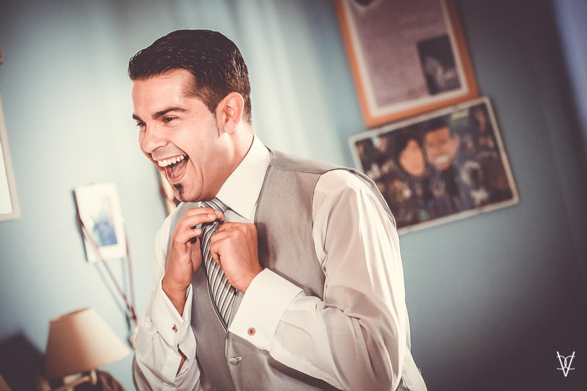 fotgraafía de novio alegre anudando corbata