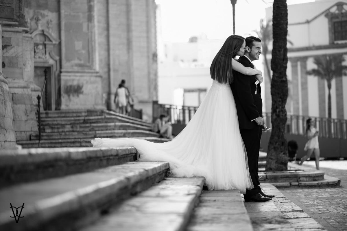 Fotos postboda en Cádiz abrazo de la novia al novio en las escaleras de la Catedral