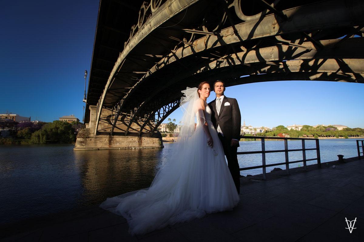 Fotos de boda en Sevilla plano general novios bajo el puente de Triana