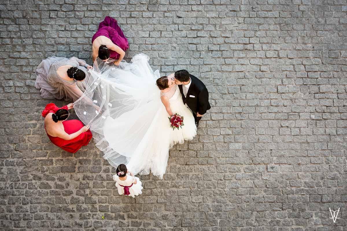Fotos de boda en Sevilla Beso de novios y arreglos del traje de novia