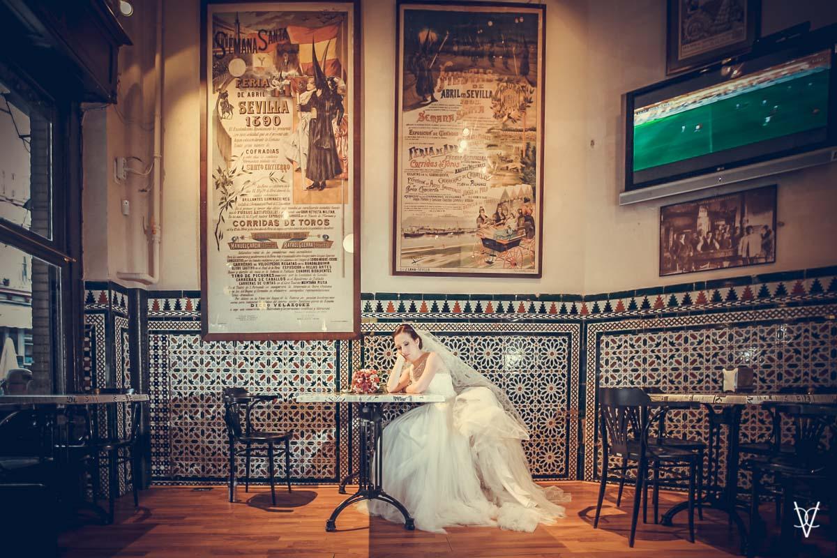 Fotos de boda en Sevilla novia sentada en mesa bar